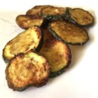 Easy Baked Zucchini Chips - Thinly sliced zucchini are tossed in olive oil and baked in this quick and easy zucchini chip recipe that adults and kids will love.