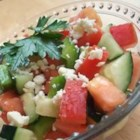Greek Salad IV - Chopped veggies  - tomatoes, red onions, cucumbers, and green peppers. But in this version, the dressing is crisper  - only olive oil with a splash of lemon juice. Chill and just before serving, sprinkle crumbled feta on top.
