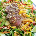 Easy Sirloin Thai Salad - Tender Sirloin on a bed of crisp salad greens and fresh mango paired with avocado and bell peppers. All topped with a delicious Thai dressing.