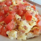 Something Interesting with Egg - Bread cubes are topped with creamy scrambled eggs, ham, tomato, and cucumber in this quick and easy breakfast that your family will love.