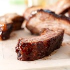 Raspberry Chipotle Back Ribs - Seasoned with a spicy dry rub, these slow-grilled tender pork back ribs are brushed with a raspberry-chipotle sauce.