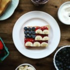 Red, White, and Blue Flag Toast - Thick slices of toast are topped with cream cheese, dotted with blueberries to stand in for the stars, with 'stripes' of bananas on a field of strawberry jam for a fun patriotic snack.