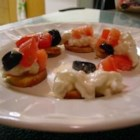 Two Layer Greek Dip - Plain yogurt and cream cheese blended with garlic and feta cheese, topped with tomatoes, cucumber, and black olives. Best with pita wedges.