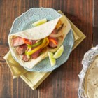 Grilled Beef Fajitas - Beef top round steak marinated in fajita seasoning is grilled, sliced, and served wrapped in tortillas with grilled peppers and onions and topped with salsa.