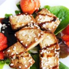 Baked Tofu Bites on a Bed of Leafy Romaine - A simplified baked tofu-bite recipe served on a bed of leafy romaine, spritzed with raspberry vinaigrette, and garnished with fresh sliced strawberries.