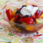 Summer Fruit Salad with Whipped Cream - Use raspberry-flavored liqueur to bring extra flavor to the fruit salad and the whipped cream topping in this summertime salad recipe.