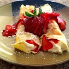 Creamy Strawberry Crepes - These delicate crepes are rolled up with a fluffy cream cheese filling and sliced strawberries. Make these as a dessert treat during strawberry season, or for a fancy weekend brunch.