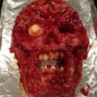 "Halloween Zombie Meatloaf - Meatloaf in the shape of a skull with hard-boiled eggs for the ""eyes"" and garlic for the ""teeth"" is a creepy and kid-friendly meal for Halloween."