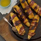 Grilled Bacon-Wrapped Corn on the Cob - Ears of corn are sprinkled with seasonings, wrapped in bacon, and grilled for a savory treat to serve at your next barbecue.