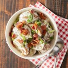 Slow-Roasted Potato Salad with Bacon - New potatoes and bacon are grilled in foil packets, then tossed in a sour cream and mustard dressing with scallions.