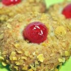 Cherry Winks - Cookies are rolled in crushed corn flakes and topped with a quarter of a maraschino cherry.