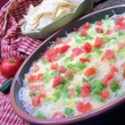 Festive Bean Spread - This is a wonderful appetizer, a bean spread with a Mexican taste. It looks very festive with the red and green toppings, and it's easy to put together. Your guests will be asking for the recipe, so keep it handy ! The two cheeses can be substituted with one 3-cup package shredded taco cheese.