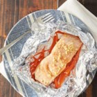 Ginger Sesame Salmon - Salmon and grated ginger with sesame oil are cooked on a bed of chopped carrots, then served on fresh spinach leaves.