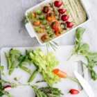 "Spring Herb Hummus Vegetable Garden - Kids will eat their vegetables when you make this adorable vegetable garden made with herbed hummus as the ""grass"" with the vegetables planted in rows."