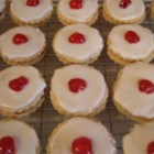 Empire Biscuits - This shortbread cookie is a traditional Scottish recipe. These are round cookies sandwiched with jam and topped off with a delicious icing and a cherry.
