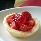 Mini Strawberry Tarts - Cream cheese pastry crusts are filled with fresh strawberries and a strawberry gelatin glaze to make cute mini tarts.  Top each with a dollop of whipped topping for an impressive presentation.