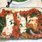 Baked Haddock with Spinach and Tomatoes - This delicious baked haddock is prepared with spinach and diced tomatoes, then smothered in a rich, tangy tomato sauce.