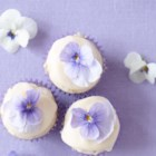 Mini Coconut Cupcakes with Passion Fruit Icing - These mini coconut cupcakes topped with passion fruit icing and edible flowers are a tropical addition to your dessert repertoire.