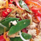 Spicy Tofu Stir Fry - Tofu, rice noodles, bell peppers, and snow peas are stir fried and spiced with a chili garlic paste to make this recipe for spicy tofu stir fry.