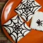 Spider Web S'mores - Graham crackers are topped with marshmallow fluff and decorated with chocolate in the shape of spider webs in these Halloween-inspired s'mores.
