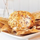 Greek-Style Cheese Ball - A variety of cheeses and herbs are rolled into balls and coated in pine nuts for a Greek-inspired cheese ball perfect for Christmas parties.