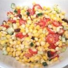 Creamy Cherry Tomato Salad with Fresh Basil, Corn and Onion - This cherry tomato-corn salad flavored with raisins and basil holds up well for summer picnics. Simply cut the raw corn from the cob -- no need to even cook it. Raisins are a surprise sweet addition.
