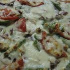Garlic Chicken Pizza - A true gourmet pizza, made even better because it's fast, easy, and inexpensive! Grilled chicken, tomato wedges, red onions, and green peppers topping a garlic-parmesan sauce and mozzarella - it's the most beautiful pizza you'll ever see...or eat!
