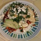 Greek Cowboy Hash and Eggs - A spicy mixture of sweet potato, garlic, and onion is topped with pan-fried eggs, cilantro, feta cheese, and avocado for a tasty breakfast indulgence.