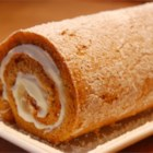 Pumpkin Roll Cake - A thin pumpkin cake, rolled around in a white cream filling, then in nuts. Can be frozen and served chilled. Dust with confectioners' sugar, if desired.