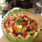 Watermelon Fruit Bowl - All of your favorite fruits, lightly sweetened, served in a watermelon 'bowl'. Try cutting a scalloped, or sawtooth, rim around the edge of the watermelon for a special presentation.