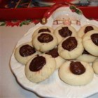 Buried Cherry Cookies - A delicious variation of the thumbprint cookie, these almond-flavored cookies are rolled into balls and given a thumbprint dent which is filled with a maraschino cherry. A dollop of chocolate frosting covers the cherry for a surprise delight.
