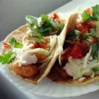 Fish Tacos - Beer battered cod are the star of these fresh and tasty fish tacos, served in corn tortillas with shredded cabbage and a zesty white sauce.