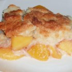 Easy Peach Cobbler - Sweetened peaches are piled into a baking pan, sprinkled with cinnamon, and topped with yellow cake mix. Cubes of cream cheese and butter are then added, and the cobbler is baked until golden and bubbly.