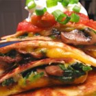Spinach and Mushroom Quesadillas - Flour tortillas filled with creamy Cheddar cheese, portabella mushrooms, and spinach. Cut in fours and serve with guacamole and sour cream. Enjoy