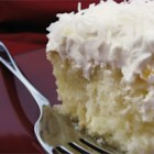 Coconut Poke Cake - White cake soaked in sweet creamy coconut milk and smothered in whipped topping and flaked coconut. A real treat for those with a sweet tooth.