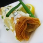 Phyllo-Wrapped Halibut Fillets with Lemon Scallion Sauce - The flaky phyllo crust keeps the halibut moist and delicious in this surprisingly simple, yet elegant recipe.