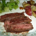 Flank Steak with Garlic Wine Sauce - Freshly roasted garlic adds great flavor to this simple but distinctive rendition. Red wine is reduced with the pan juices for the sauce.