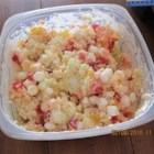 Fruity Acini di Pepe Salad - Tiny pearls of acini di pepe in a fruity custard, tossed with crushed pineapple, mandarin oranges, whipped topping and mini marshmallows, make a bright, refreshing pasta salad. Maraschino cherries add eye-popping color.