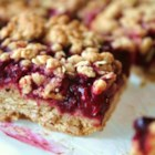 Delicious Raspberry Oatmeal Cookie Bars - Seedless raspberry jam is sandwiched between buttery brown sugar-oatmeal cookie crusts.