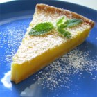 Tart Lemon Triangles - Lemon bars with both lemon juice and lemon zest, baked in a pie plate. Garnish with whipped cream and strawberries, if desired.