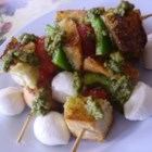 Panzanella Salad Skewers - Grilled bread salad! Callisons seasoned skewers threaded with artisanal bread, fresh mozzarella, and vegetables are served on a bed of romaine lettuce and dressed with basil pesto.