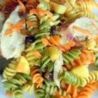 Curry Pasta Salad - Raisins, carrots, pine nuts and tofu are tossed with colorful pasta spirals and blanketed with an aromatic blend of curry powder, lemon juice and mayonnaise or yogurt for a scintillating summer salad.
