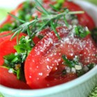 Sliced Tomatoes with Fresh Herb Dressing - Sliced tomatoes are marinated in olive oil with chopped fresh thyme, oregano, parsley, chives and garlic, then topped with Parmesan cheese to make a garden-fresh side dish.