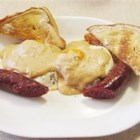 Cajun-Style Eggs Benedict - Forget the English muffins, Canadian bacon, poaching eggs, and harassing Hollandaise sauce.  This biscuit, egg, and andouille sausage breakfast topped with a simple Mornay sauce is terrific.