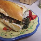 Portabella Basil Sub - A savory mixture of portabella mushrooms, spinach, basil, and yellow bell pepper in a piquant sauce is piled high on a hoagie bun and served hot.