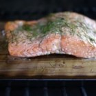 Cedar Plank-Grilled Salmon with Garlic, Lemon and Dill - Cooking a lemon and dill seasoned whole salmon fillet on a smoldering cedar plank adds a touch of smoke to a beautiful fish!