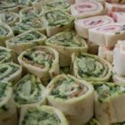 Spinach Roll-Ups - The popular recipe for sour-cream-based spinach dip turns up in a tortilla here--rolled and sliced into bite-size pinwheels.