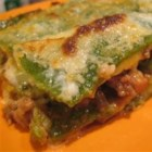 Lasagne Verdi al Forno - Homemade sheets of spinach pasta are layered with a rich meat ragu, bechamel sauce, ricotta, and Parmesan and baked until golden and bubbly. A delicious recipe from the Emilia-Romagna region of Italy.