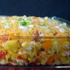 Mexican Cornbread Salad - This layered salad is made with green chile cornbread, pinto beans, peppers, corn, bacon bits, tomatoes, and cheese. It's then chilled for two hours to allow the flavors to blend.