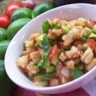 Avocado Shrimp Ceviche-Estillo Sarita - Shrimp is marinated in lime juice to cook, then mixed with tomato, cilantro, onion and a special sauce. You can save a couple of whole shrimps to dangle on the edge of the tumbler for a special presentation. The lime and the cilantro are the key, and of course fresh shrimp.